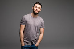 Portrait of a smart serious young man in casual clothes standing. Against grey background royalty free stock photo