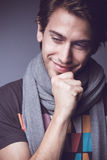 Handsome young man smiling. Portrait of handsome smiling young man having happy thoughts on gray background Stock Image