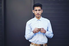 Portrait of smart student in trendy wear standing against promotional background Royalty Free Stock Image