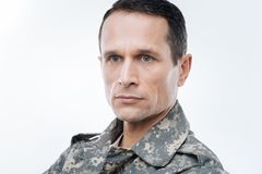 Portrait of a smart thoughtful serviceman. US navy. Portrait of a smart nice thoughtful serviceman standing against while background while thinking about the Stock Images