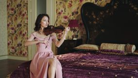 Portrait of smart violinist playing the melody in bedroom. Beautiful portrait of smart violinist sitting on bed and playing the melody in bedroom in evening. 4K stock video footage