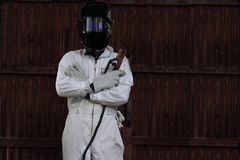 Portrait of smart welder man with torch and protective helmet in white uniform in the factory. Industrial concept. Stock Photography