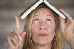 Portrait smart woman with book on head Stock Image
