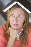 Portrait smart woman thinking with book on head Stock Photography