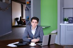 Portrait of smart young guy student who posing and looking in ca. Portrait of self-assured male businessman who possing in camera and smilling, sitting at table Royalty Free Stock Images