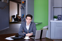 Portrait of smart young guy student who posing and looking in ca. Portrait of self-assured male businessman who possing in camera and smilling, sitting at table Stock Photo