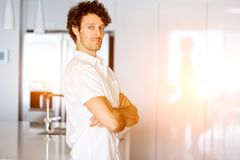 Portrait of a smart young man standing in kitchen Stock Image
