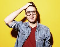 Portrait of young smiling man standing against yellow background. Portrait of a smart young smiling man standing against yellow background Stock Image