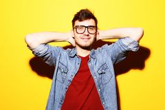 Portrait of young smiling man standing against yellow background. Portrait of a smart young smiling man standing against yellow background Stock Photography