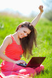 Portrait of a smart young woman lying on grass and using laptop Stock Photography
