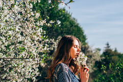 Portrait of smelling a bouquet of flowers young girl in cherry g Stock Images