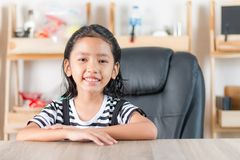 Portrait of Asian little girl sitting at wooden table Royalty Free Stock Photography