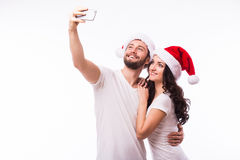Portrait smile couple in Santa hats in love taking romantic self portrait. Christmas young beautiful couple in Santa hats in love taking romantic self portrait Stock Image