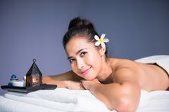 Happy woman having oil spa massage. Portrait of Smile young Asian Thai girl relax in spa. Body care treatment. Cute tan beautiful happy woman having oil massage Stock Image