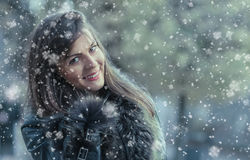 Portrait of a smile young woman in a winter snow day. Girl wearing fur and looking to camera trough snowflakes Royalty Free Stock Images