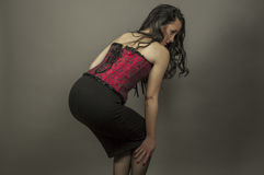 Portrait of smiley beautiful woman with red corset caress her le Stock Photo