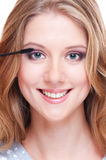 Portrait of smiley woman applying make up Stock Photography