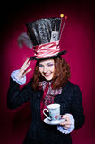 Portrait of smilimg young woman in the similitude of the Hatter. (Alice's Adventures in Wonderland) with cup of tea royalty free stock image