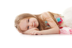 Portrait of smiling adorable girl lying in studio stock images