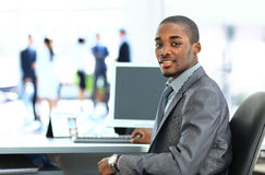 Portrait of smiling African American business man. With executives working in background Stock Photo