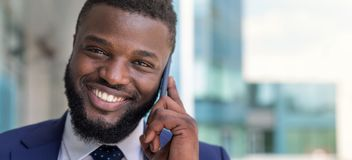 Portrait of smiling african american businessman speaking by phone outdoors. Copy space stock image