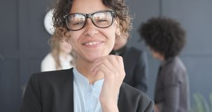 Portrait of smiling african american businesswoman. Smiling african american businesswoman with colleagues in the background stock video footage