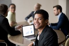 Portrait of smiling African American employee posing at meeting. Portrait of smiling African American male employee posing for picture during office business stock photo