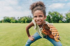 Child playing baseball in park. Portrait of smiling african american little girl with baseball glove playing baseball in park Royalty Free Stock Image