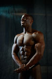 Portrait of smiling african american male bodybuilder with naked torso posing on a black studio background. Human's body. Perfection Stock Photos
