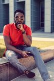 Portrait of serious black man in a red t shirt. Portrait of smiling african american male in a red polo t shirt stock images
