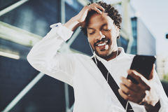 Portrait of Smiling African American man in headphones standidng in sunny street enjoying to music on his smart phone Stock Photos