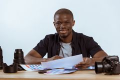 Portrait of smiling african american photographer sitting at workplace with photoshoot examples and photo camera and looking. At camera royalty free stock image