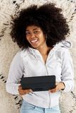 Smiling african girl lying on floor with digital tablet. Portrait of smiling african girl lying on floor with digital tablet Stock Photography