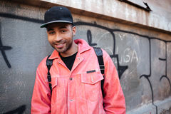 Portrait of a smiling african guy in cap with backpack Stock Image