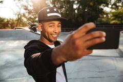 Portrait of a smiling african male teenager taking a selfie. While holding a skateboard on his shoulders outdoors Stock Image