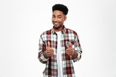Portrait of a smiling african man dressed in plaid shirt. Portrait of a smiling young african man dressed in plaid shirt showing two thumbs up isolated over Royalty Free Stock Photos