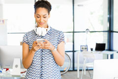 Portrait of smiling afro-american office worker with her mobile phone in offfice Royalty Free Stock Photography