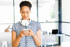 Portrait of smiling afro-american office worker with her mobile phone in offfice Royalty Free Stock Image