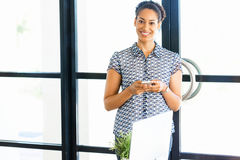 Portrait of smiling afro-american office worker with her mobile phone in offfice Stock Images