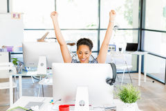 Portrait of smiling afro-american office worker in offfice holding her arms up. Portrait of beautiful smiling afro-american office worker in office holding her royalty free stock image
