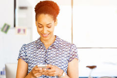 Portrait of smiling afro-american office worker in offfice with mobile Royalty Free Stock Photos