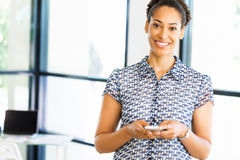 Portrait of smiling afro-american office worker in offfice with mobile Stock Photos