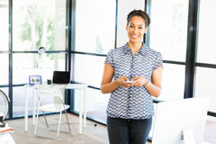 Portrait of smiling afro-american office worker in offfice with mobile Stock Photography