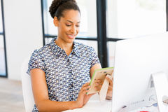 Portrait of smiling afro-american office worker sitting in offfice Stock Image