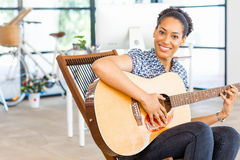 Portrait of smiling afro-american office worker sitting in offfice with guitar Royalty Free Stock Image