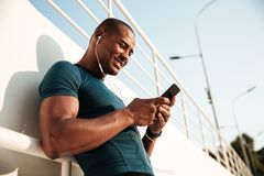 Portrait of a smiling afro american sportsman listening to music. With earphones while using mobile phone and leaning on a wall outdoors Stock Photos