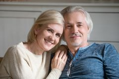 Portrait of smiling aged couple making family picture stock photo