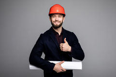 Portrait of a smiling architect in hard hat with blueprint gesturing thumbs up on grey. Portrait of a smiling architect in hard hat with blueprint gesturing Royalty Free Stock Photography
