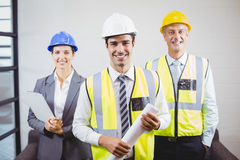 Portrait of smiling architects with blueprint. While standing in building Stock Photography