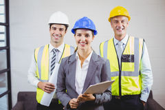 Portrait of smiling architects with clipboard. While standing in building Royalty Free Stock Image